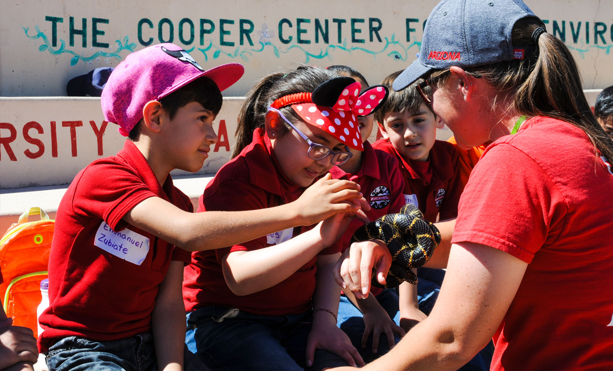 Camp Cooper half day programs include an animal experience - photo of children learning about a king snake.